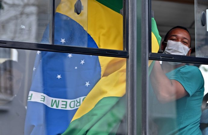 A Brazilian citizen shows a national flag from a bus taking him and others to the Jorge Chavez international airport in Callao, outside the Brazilian consulate in Lima, on March 20, 2020, due to coronavirus lockdown. - Some 400 Brazilian citizens are being repatriated after remaining stranded due to the closure of borders and the mandatory quarantine decreed by the Peruvian government as a preventive measure against the coronavirus pandemic. 263 people have tested positive and four have died in Peru so far from the new coronavirus, COVID-19. (Photo by Cris BOURONCLE / AFP)