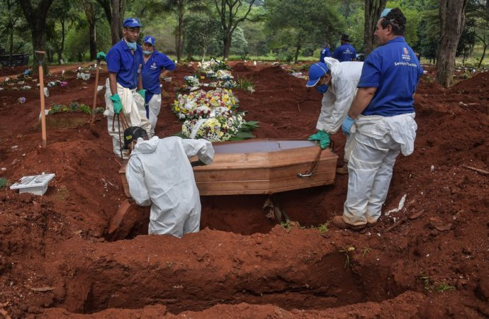 Employees bury a person who died suspectedly from COVID-19 at the Vila Formosa cemetery, in the outskirts of Sao Paulo, Brazil on March 31, 2020. - Vila Formosa cemetery, the largest in Latin America with an area of 780 thousand square meters and where more than 1.5 million people were buried, had a 30% increase in the number of burials after the beginning of the COVID-19 pandemic. (Photo by NELSON ALMEIDA / AFP)